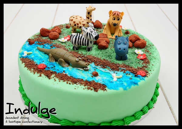 wild animals childrens sponge cake with sugar paste icing and decorated with edible figurines
